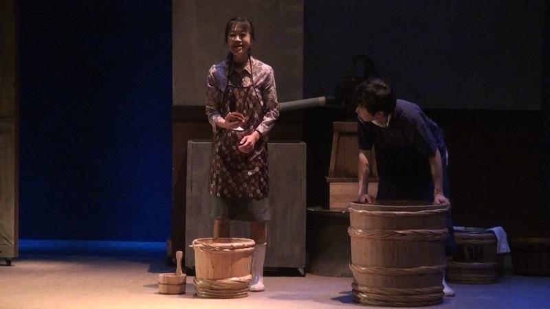 泉商店の庭で桶を洗う久里子と村松